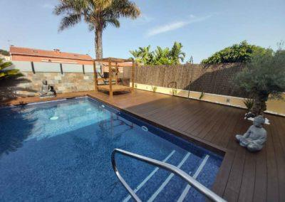 Tarima de bambú en jardín con piscina