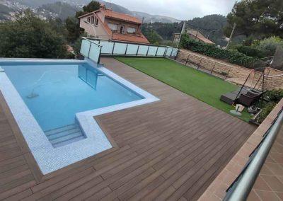 Tarima exterior tecnológica en jardín con piscina